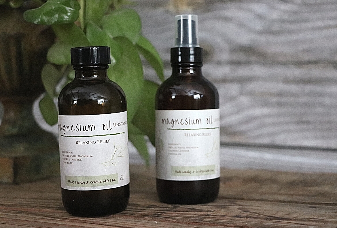 Magnesium Oil Benefits, Uses, And DIY Spray Recipe image showing 2 bottles of magnesium oil spray in front of wooden board and greenery